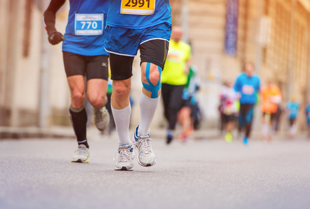 injured knee: Unrecognizable young runner with injured knee at the city race