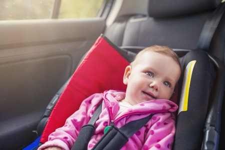 red chair: Little baby girl in a car in a child seat