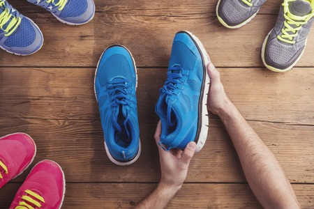 Man holding a pair of running shoes on a wooden floor background