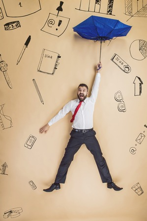 calamity: Handsome manager with umbrella falling down. Studio shot on beige background. Stock Photo