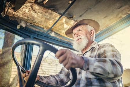 old man beard: Senior man at the farm driving an old tractor