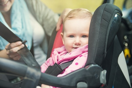 child seat: Mother in a car, having her little baby girl in a child seat