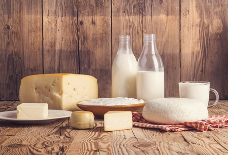 Variety of dairy products laid on a wooden table background Stockfoto