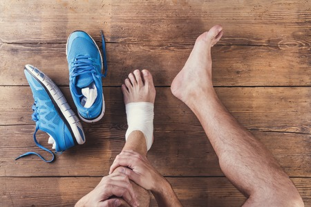 leg injury: Unrecognizable injured runner sitting on a wooden floor background Stock Photo