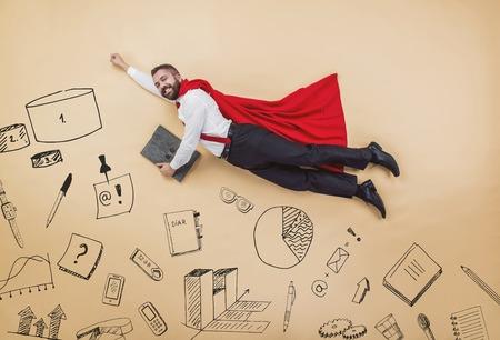 赤いマントを着てスーパー ヒーロー ポーズ マネージャー。スタジオは、ベージュの背景に撮影。
