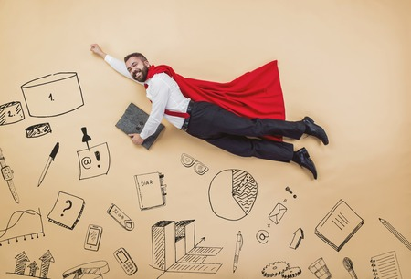 moving office: Manager in a superhero pose wearing a red cloak. Studio shot on a beige background. Stock Photo