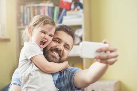 father with child: Young father with his cute little daughter taking selfie Stock Photo