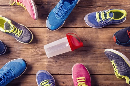 Various running shoes laid on a wooden floor background photo