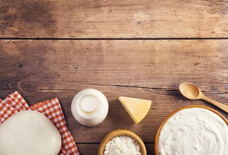 leche y derivados: Variedad de productos lácteos colocó en un fondo de la tabla de madera