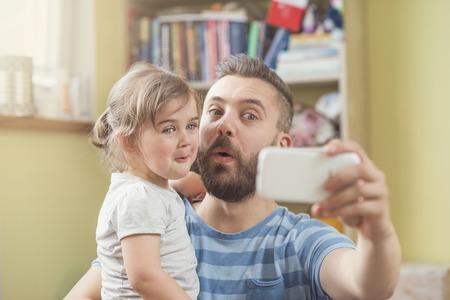padre e hija: Padre joven con su pequeña hija teniendo selfie lindo Foto de archivo