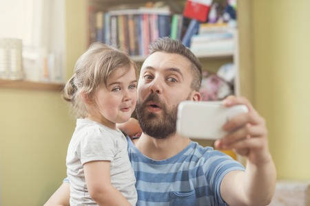 father and child: Young father with his cute little daughter taking selfie Stock Photo