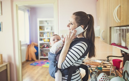 sling: Young mother talking on a phone having her baby in a carrier Stock Photo