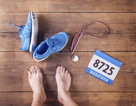 bare foot: Legs of a runner, medal and race number on a wooden floor background