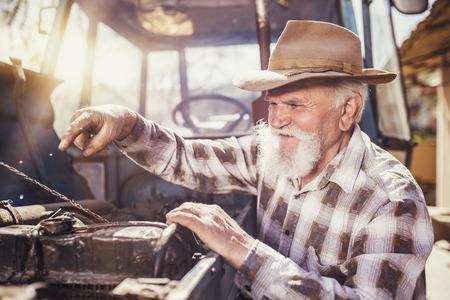 busy beard: Senior man at the farm repairing an old tractor