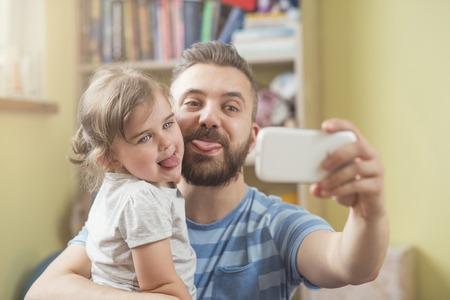 ni�os inteligentes: Padre joven con su peque�a hija teniendo selfie lindo Foto de archivo