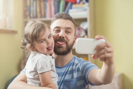dad and daughter: Young father with his cute little daughter taking selfie Stock Photo