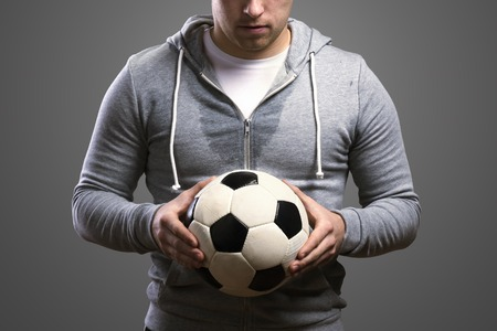 Young sportsman holding a soccer ball. Studio shot on gray background. photo