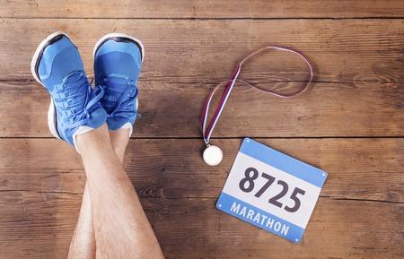 atleta corriendo: Las piernas de un número de corredor, medalla y la raza en un fondo de suelo de madera Foto de archivo