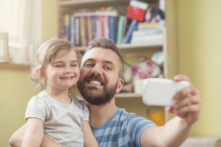 Young father with his cute little daughter taking selfie photo