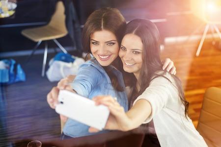 Two beautiful women taking selfie in cafe Stock Photo