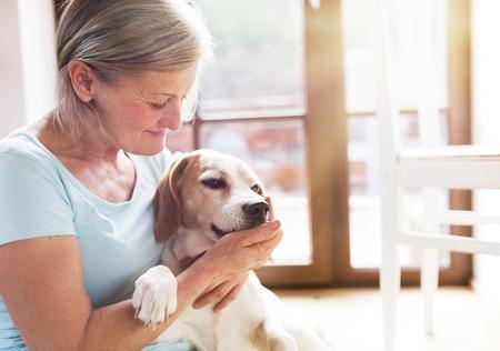 Ältere Frau, die mit ihrem Hund in ihr Haus.