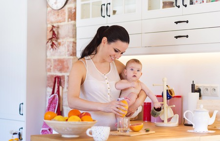 citrus family: Cute little baby in the arms of her mother in their kitchen. Stock Photo