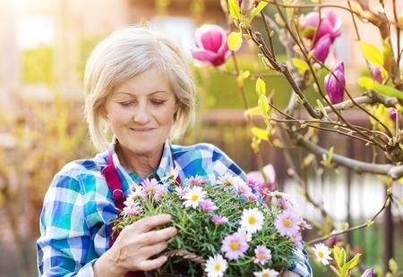 active people: Beautiful senior woman planting flowers in her garden