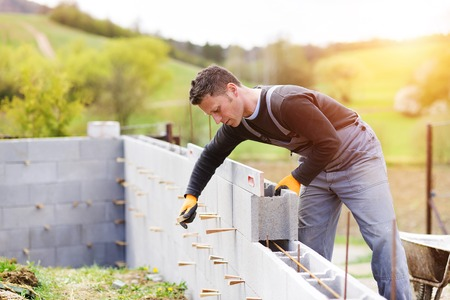 bricklayer: Bricklayer putting down another row of bricks in site