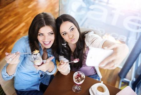 women friends: Two beautiful women taking selfie in cafe Stock Photo
