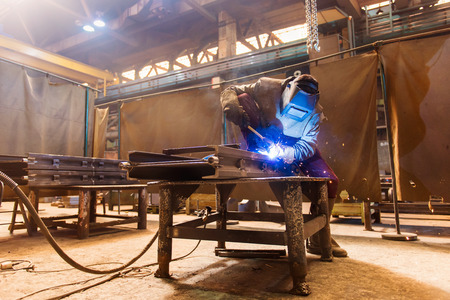 welding: Young man with protective mask welding in a factory Stock Photo
