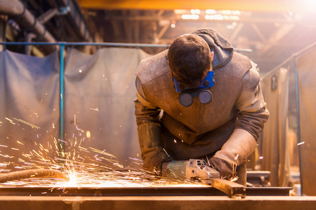 Young man with protective mask welding in a factory photo