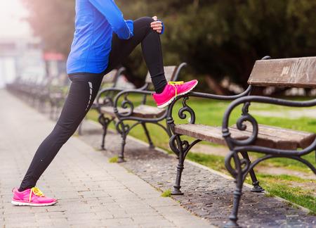 mujeres fitness: Joven corredor de estiramiento antes de la carrera de la ciudad Foto de archivo