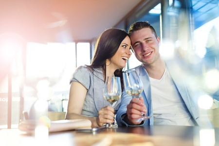 Beautiful young couple drinking wine in a bar photo