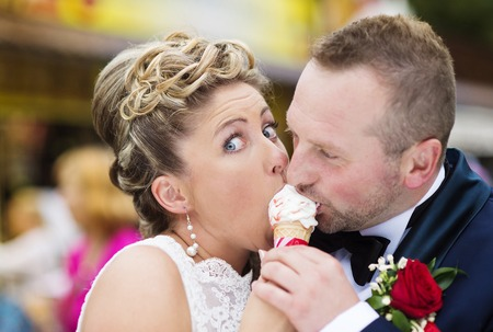 Beautiful young wedding couple enjoying ice cream