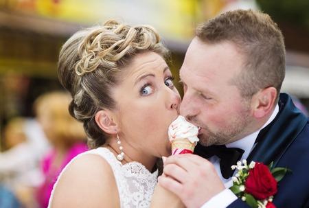 ice cream woman: Beautiful young wedding couple enjoying ice cream
