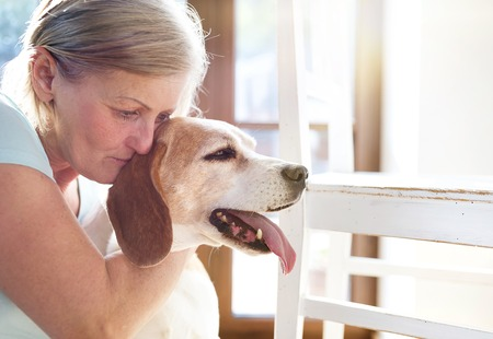 pet therapy: Senior woman with her dog inside of her house.