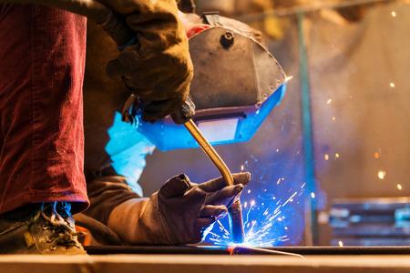 mascara de gas: Hombre joven con la máscara protectora de soldadura en una fábrica