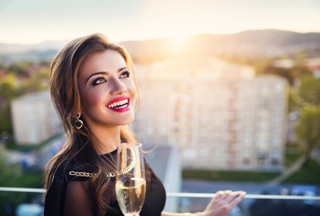 bar top: Attractive young woman with glass of champagne in a bar