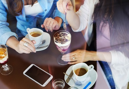 Two beautiful women drinking coffee and chatting in cafe