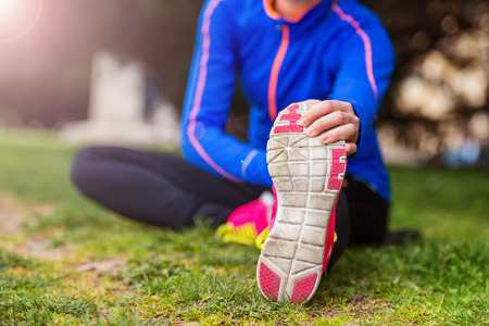 young woman legs up: Young runner stretching before the city race Stock Photo