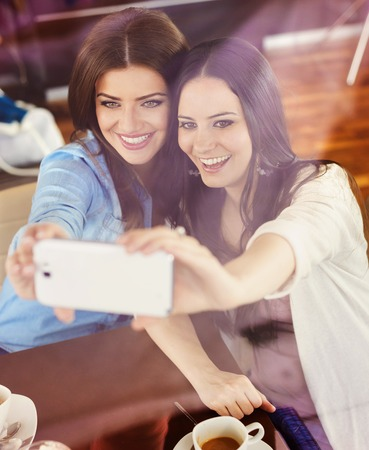 Two beautiful women taking selfie in cafe Stock Photo