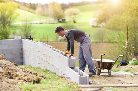 Bricklayer putting down another row of bricks in site Reklamní fotografie - 39484980