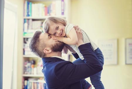 dadã  daughter: Joven padre abrazando a su hija como llega a casa desde el trabajo Foto de archivo