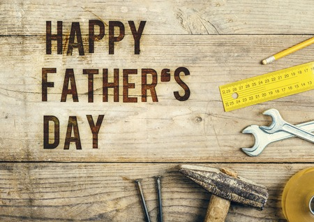 fathers day: Desk of a carpenter with Happy fathers day sign. Studio shot on a wooden background. Stock Photo