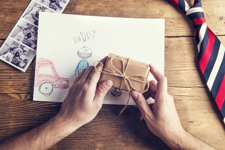pictures of father and daughter, child drawing, present and tie laid on wooden desk background. Stock Photo