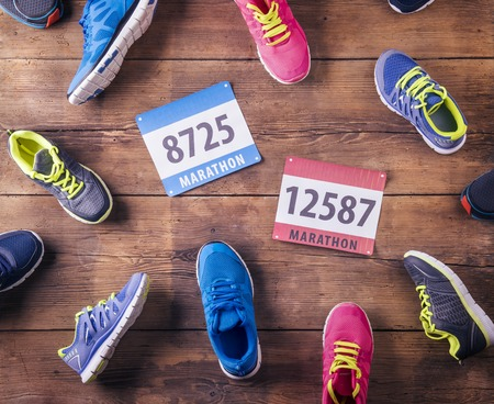 laid: Various running shoes and race numbers laid on a wooden floor background