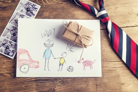 pictures of father and daughter, child\'s drawing, present and tie laid on wooden desk background. Foto de archivo