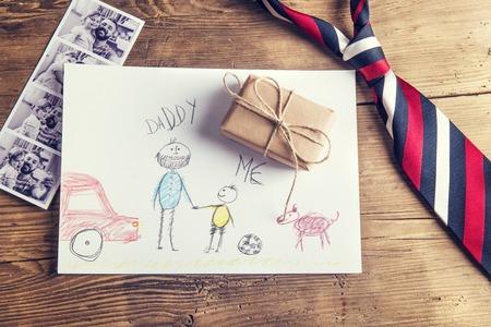 lazo regalo: fotos del padre y la hija, dibujo del niño, presente y corbata establecido en el fondo de escritorio de madera.