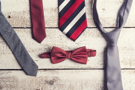 red tie: Fathers day composition of colorful ties and bow tie laid on wooden floor backround.