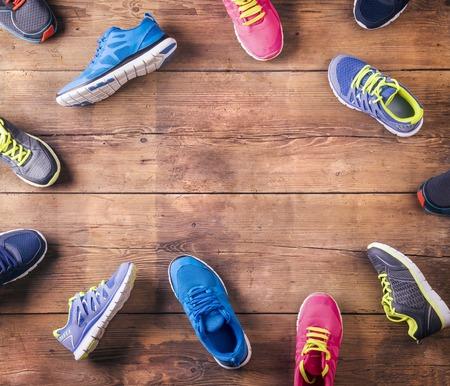 hombres corriendo: Varios zapatillas deportivas establecidas en un fondo de madera piso